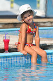 girl sitting in the pool and drinking cocktails Stock Images