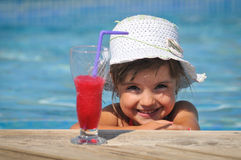 Girl sitting in the pool and drinking cocktails Stock Image