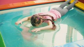 Girl sitting on the pool. Which is covered with transparent film stock video footage