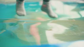Girl sitting on the pool. Which is covered with transparent film stock footage