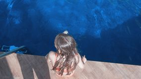 Girl sitting on pool side swaying legs in swimming pool water outdoor overhead view. Top view girl splashing legs in. Blue water swimming pool in resort stock footage