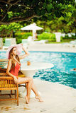 Girl sitting by a poolside Royalty Free Stock Image