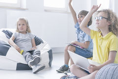 Girl is sitting in a pouf. Girl is sitting in a black and white pouf during an interesting programming lesson modern teaching concept Stock Images