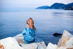 Girl sitting on the precipice sea Stock Photos