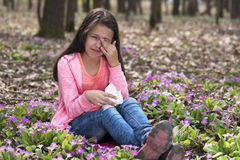 Girl sitting among primroses and rubbing her eyes Royalty Free Stock Image