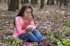 Girl sitting among primroses and sneezing Royalty Free Stock Image