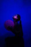 Girl sitting profile dark under UV light with ball royalty free stock photos