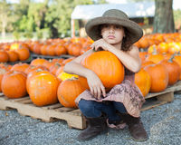 Girl sitting in a pumpkin patch Royalty Free Stock Image