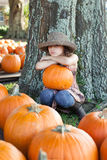 Girl sitting in a pumpkin patch Stock Image