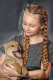 Girl sitting with a puppy in her arms Royalty Free Stock Photo
