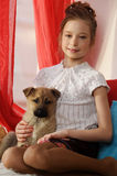 Girl sitting  with a puppy in her arms Stock Images