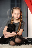 Girl sitting  with a puppy in her arms Royalty Free Stock Photos