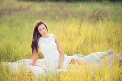 Girl sitting on quilt in field Royalty Free Stock Images