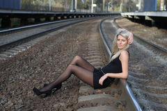 Girl sitting on rail Stock Images