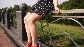 The girl is sitting on the railing and shaking her legs. Beautiful girl in a dress, carefree walks on the street. stock video