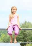 Girl sitting on railings. Smiling child - barefoot girl sitting on metal railings Royalty Free Stock Photography