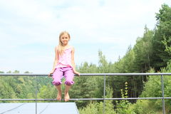 Girl sitting on railings. Smiling child - barefoot girl sitting on metal railings Stock Image