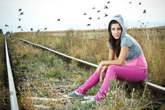 Girl sitting on railroad Stock Images