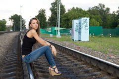 Girl sitting on rails Stock Photo