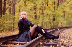 Girl sitting on rails in autumn park Stock Photography
