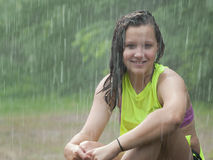 Girl sitting in the rain Stock Photography