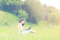 Girl sitting reading a book outdoors Royalty Free Stock Images