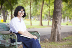 Girl sitting and reading a book. Sit on a bench in the park Stock Photo