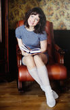 Girl sitting reading a book. The girl sits in a leather chair and reading a book Royalty Free Stock Photo