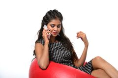Girl is sitting on red bean bag couch and talking on the phone royalty free stock photo