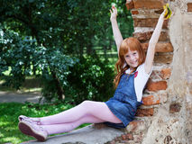 Girl sitting on the red brick wal Royalty Free Stock Photos