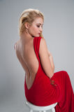 Girl sitting in a red dress with an open back and cocked. Pretty girl sitting in a red dress with an open back and cocked his head to the bottom Royalty Free Stock Image