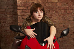 Girl sitting on a red motorcycle Stock Photos