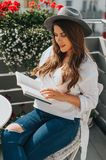 Girl, sitting relaxed on the terrace holding a book stock photography