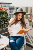 Girl, sitting relaxed on the terrace holding a book stock image
