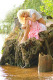 Girl sitting at river bank with head on her knees Stock Photos