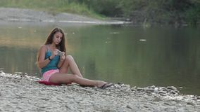 Girl Sitting on the River Bank With the Phone stock footage