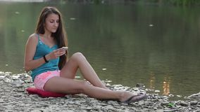 Girl Sitting on the River Bank With the Phone stock video footage