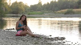 Girl Sitting on the River Bank of Phone Viewing stock video footage