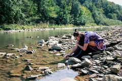 Beautiful girl is sitting on the river bank. royalty free stock photo