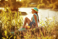 Girl sitting on the river bank Stock Photo