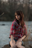 Girl sitting on a river rock Stock Photos