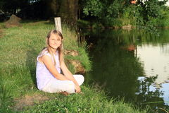 Girl sitting by a river Royalty Free Stock Images