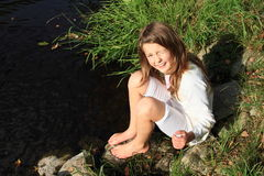 Girl sitting by a river Stock Images
