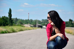 Girl sitting on the road. On the left Royalty Free Stock Photography