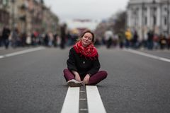 Happy girl sitting on the road in the middle of the street. stock images