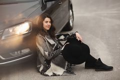 The girl is sitting on the road near a black car royalty free stock photo