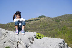 A girl sitting on a rock Royalty Free Stock Image
