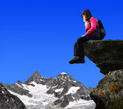 Girl sitting on a rock. In the background mount Ober Gabelhorn - Swiss Alps, Europe royalty free stock photos
