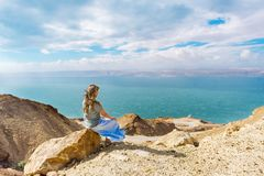 Girl sitting on the rock on the cliff watching the dead sea in Jordan. Young woman sitting on the rock on the cliff watching the dead sea in Jordan stock photos
