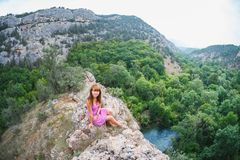 The girl is sitting on a rock. Down the river runs stock images